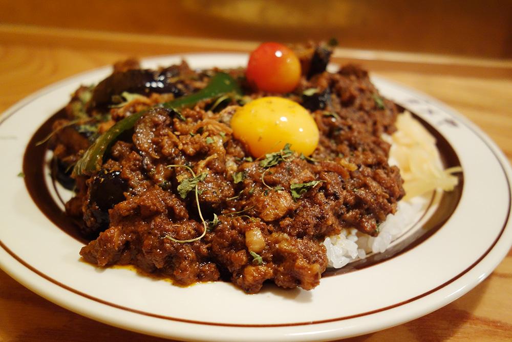 ダメヤのトリプルキーマカレー、ご飯の上にお肉がもりもりと盛られています。お肉の上には、ピーマン、トマト、生卵の黄身も。