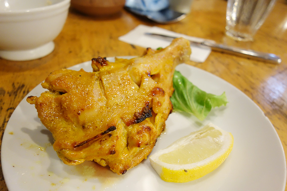 ガネーシャのタンドリーチキン、お皿にレモンと一緒に盛られています。
