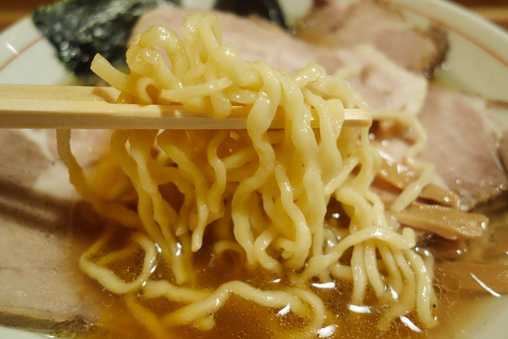 ラーメンの麺を箸で持ち上げている