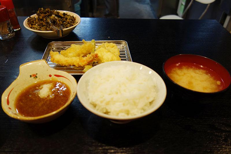 テーブルに味噌汁、ご飯、天ぷら、天ぷらのつけダレ。奥には、高菜。