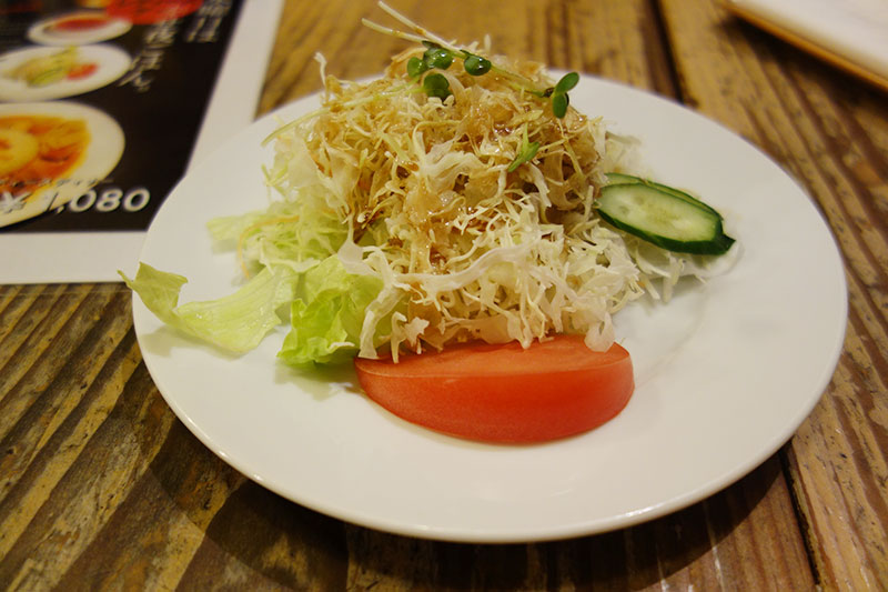白いお皿にトマト、きゅうり、千切りのキャベツが盛られてサラダ