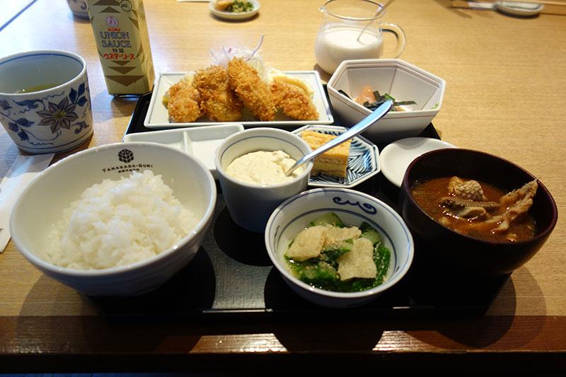 ご飯、前菜、うお汁、カキフライにお茶がテーブルに乗っています。