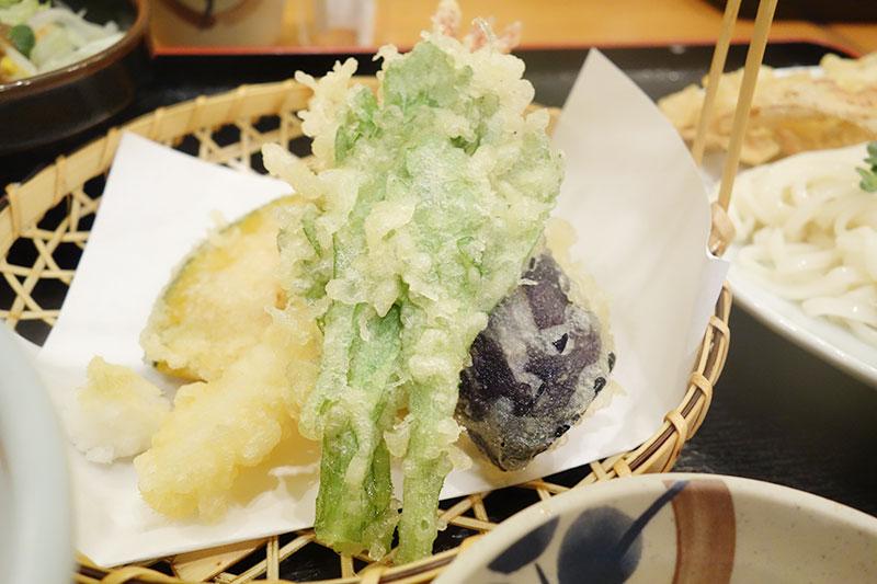 ピーマンなど、ザルの上に天ぷらが盛られています