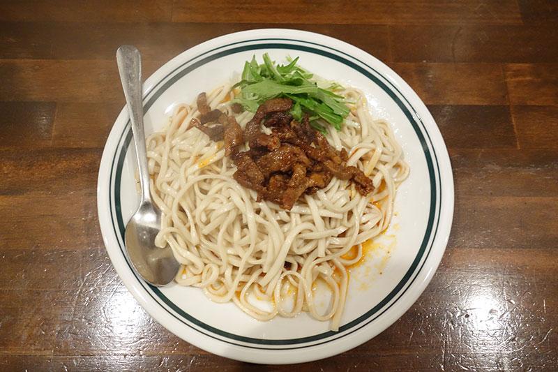 お皿に麺、麺の上に肉が乗っています。お皿にスプーンも。