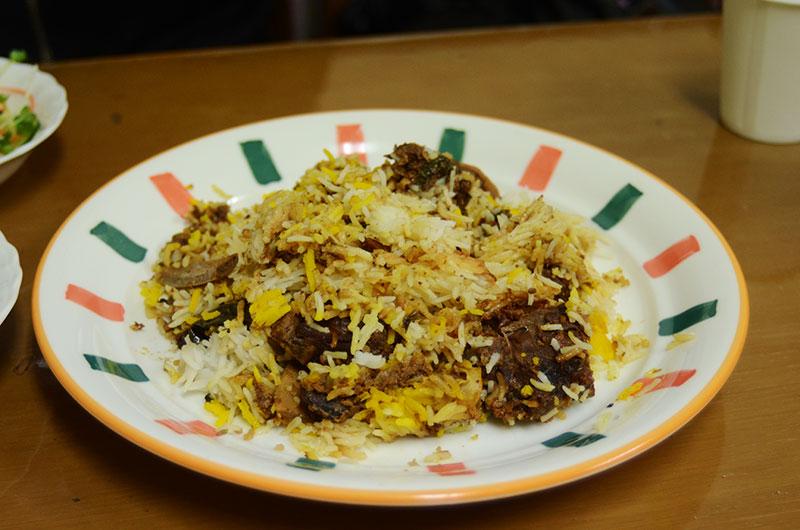 お皿に盛られたスパイス炊き込みご飯、マトンのお肉も入っています。