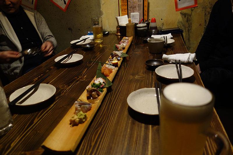 テーブルに長い竹、その上にお刺身が盛られています。