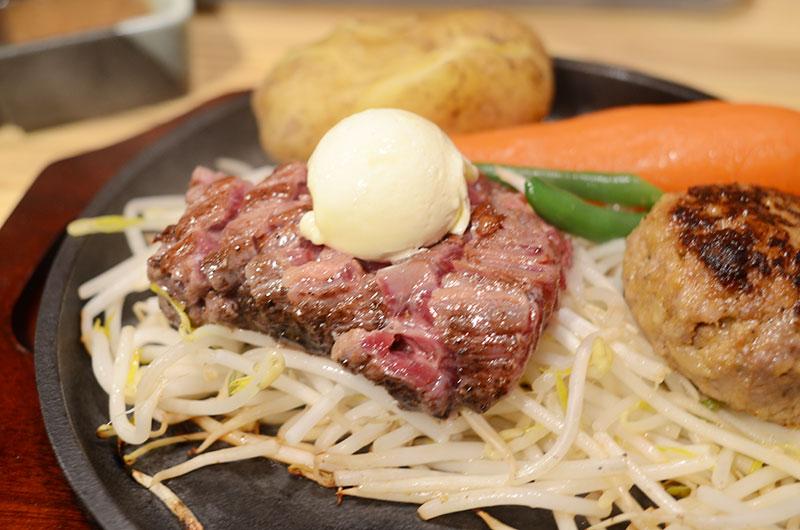 鉄板の上にモヤシ、その上に赤身のお肉。お肉の上にはガーリックバターが乗っています。